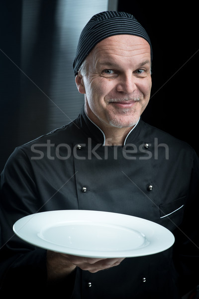 Stock photo: Chef in black uniform showing a plate