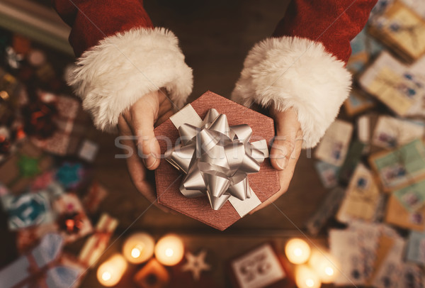 Stock photo: Santa Claus giving a Christmas present