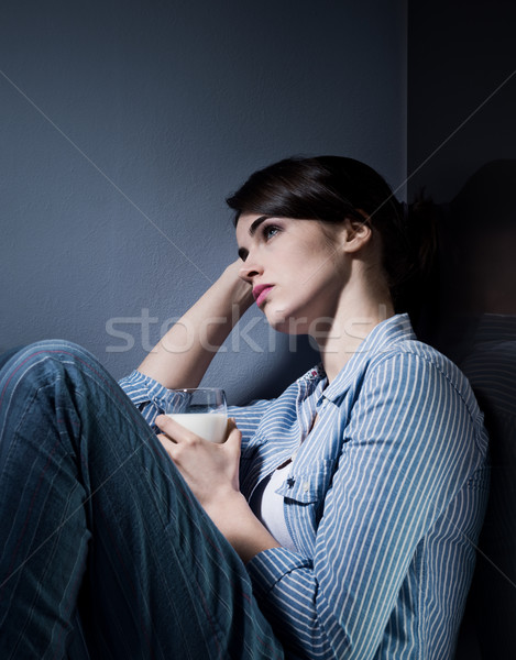 Stock photo: Sleepless woman having a glass of milk