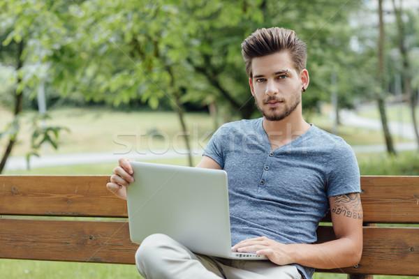 Hombre guapo usando la computadora portátil parque jóvenes relajante sesión Foto stock © stokkete