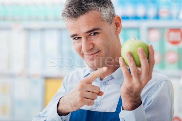 Supermarket clerk showing fresh fruit Stock photo © stokkete