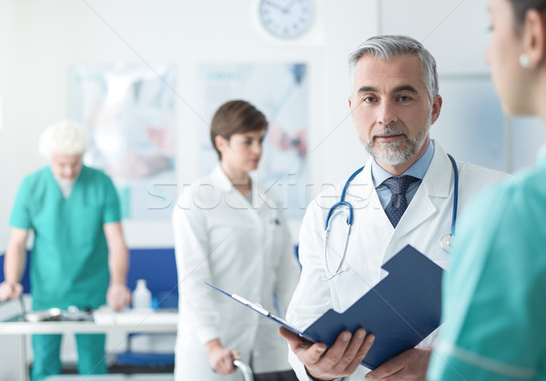 Doctor examining a patient's medical records Stock photo © stokkete