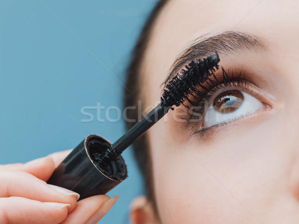 Woman applying mascara on her lashes Stock photo © stokkete