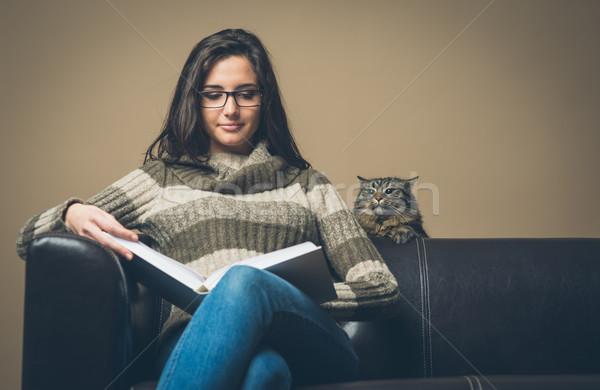 Młoda kobieta czytania książki ciekawy kot młodych Zdjęcia stock © stokkete