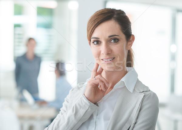 Confident woman entrepreneur posing in her office Stock photo © stokkete
