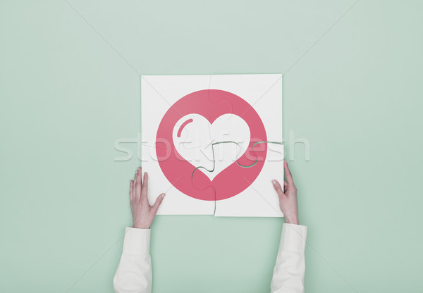 Woman completing a puzzle with heart icon Stock photo © stokkete