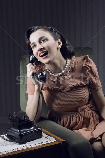 Happy woman talking on landline phone Stock photo © stokkete
