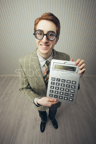 A nerdy guy with a giant-sized calculator  Stock photo © stokkete