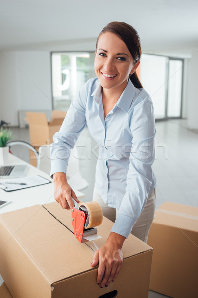 Businesswoman taping up a cardboard box Stock photo © stokkete