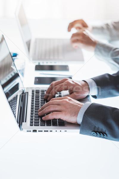 üzletemberek dolgozik laptopok profi üzletemberek irodai asztal Stock fotó © stokkete