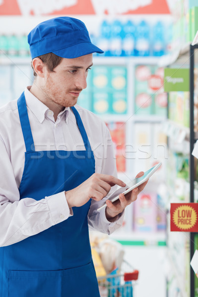 Supermarket clerk working with a tablet Stock photo © stokkete