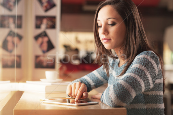 Young woman at the bar using a tablet Stock photo © stokkete