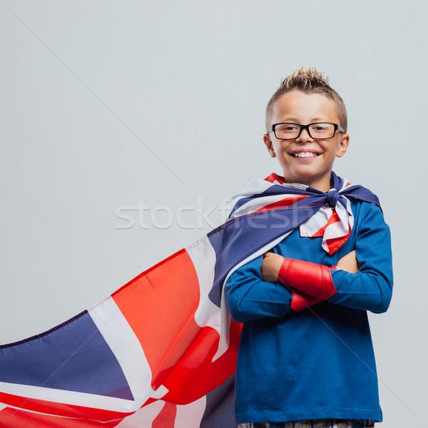 Mosolyog szuperhős fiú brit zászló áll karok Stock fotó © stokkete