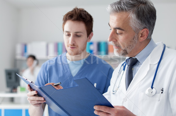 Doctors examining patient's medical records Stock photo © stokkete