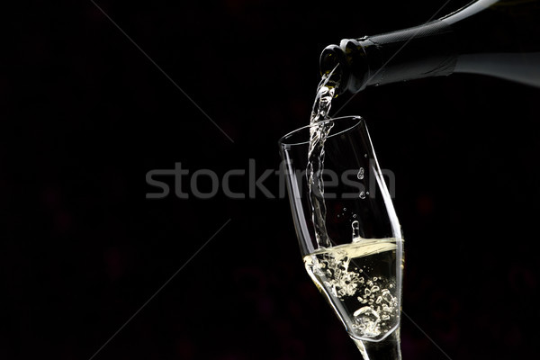 Pouring white wine into a wineglass Stock photo © stokkete