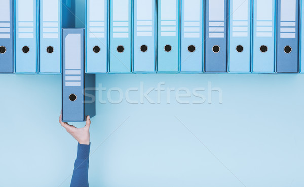 Office worker taking a folder in the archive Stock photo © stokkete