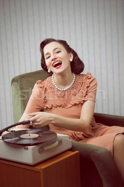 Stock photo: Young woman listening to music from a turntable