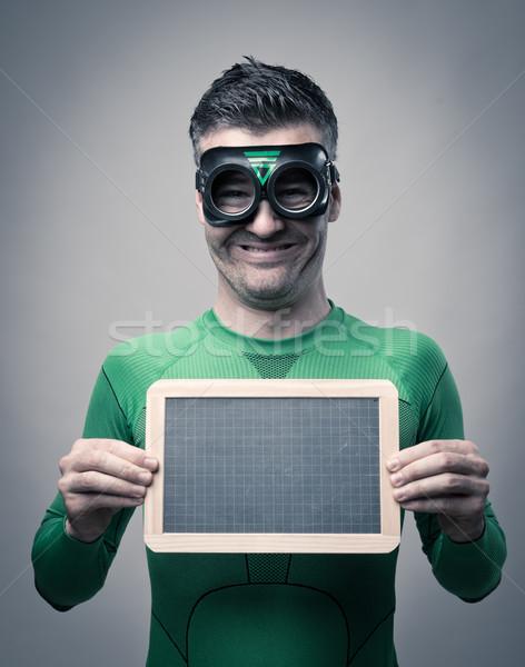 Cheerful superhero holding a blackboard Stock photo © stokkete