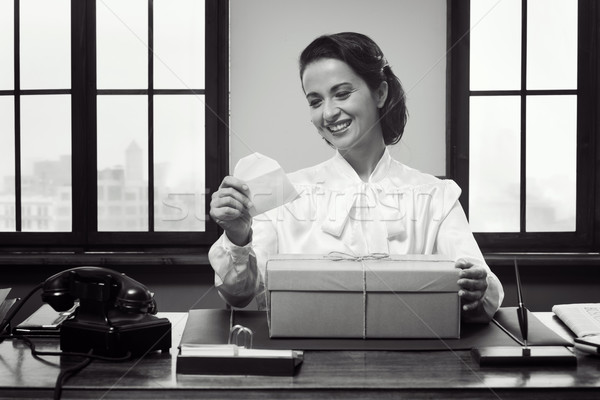Smiling woman receiving a gift box by mail Stock photo © stokkete