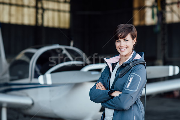 Smiling female pilot posing with her plane Stock photo © stokkete