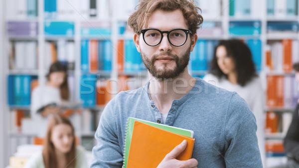 Hipszter egyetemi hallgató tart jegyzetfüzetek mosolyog diákok Stock fotó © stokkete