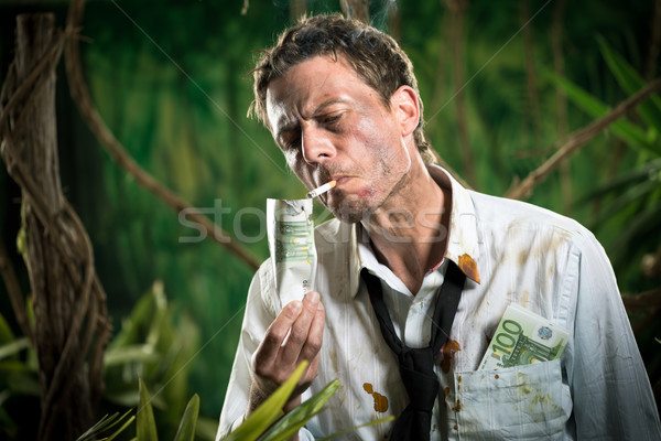 Businessman lighting a cigarette with a banknote Stock photo © stokkete