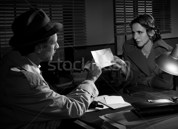Woman handing over an envelope to a detective Stock photo © stokkete