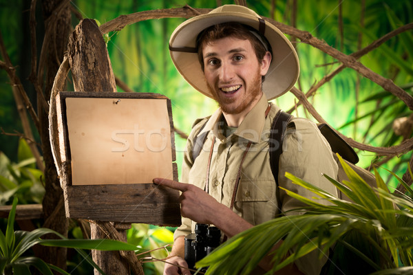 Cheerful explorer with sign Stock photo © stokkete
