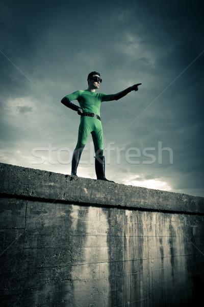 Superhero pointing with dramatic background Stock photo © stokkete