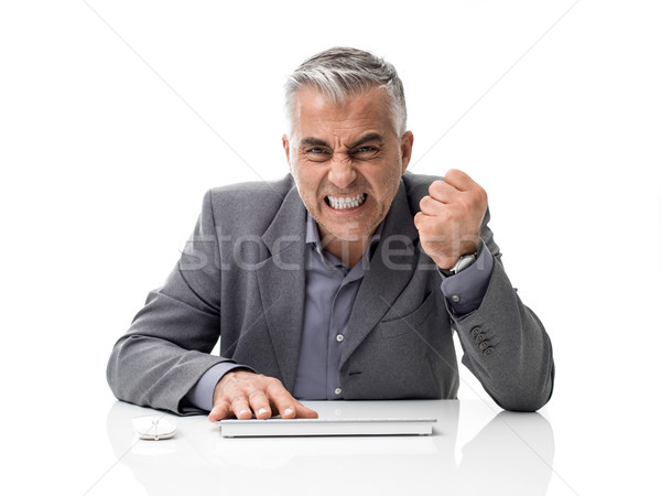 Angry businessman working with a computer Stock photo © stokkete