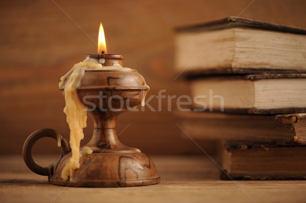old candle on a wooden table, old books in the background Stock photo © stokkete
