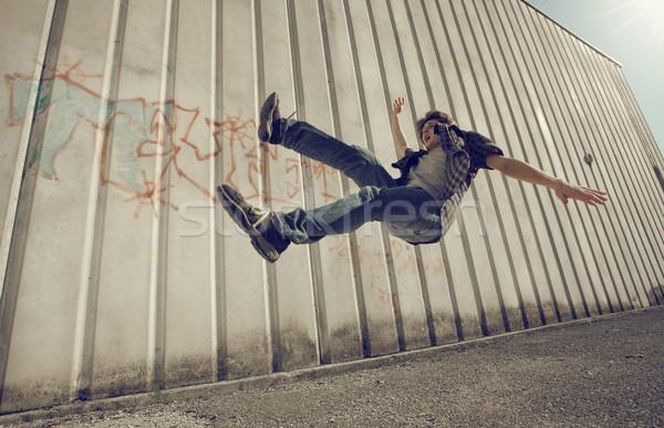 Automne vers le bas jeune homme relevant mur jeans Photo stock © stokkete