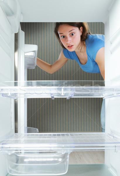 Boş buzdolabı genç kadın bakıyor kız buzdolabı Stok fotoğraf © stokkete