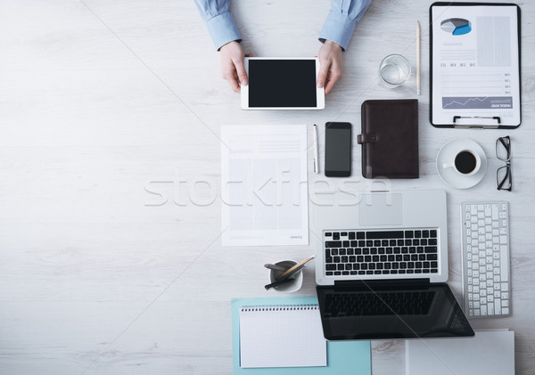 Businessman working at desk with a digital tablet Stock photo © stokkete