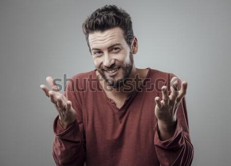 Confundirse hombre joven sonriendo cámara manos Foto stock © stokkete