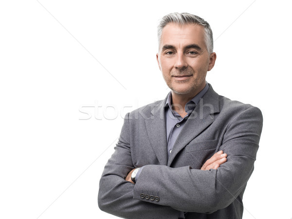 Confident businessman posing with arms crossed Stock photo © stokkete