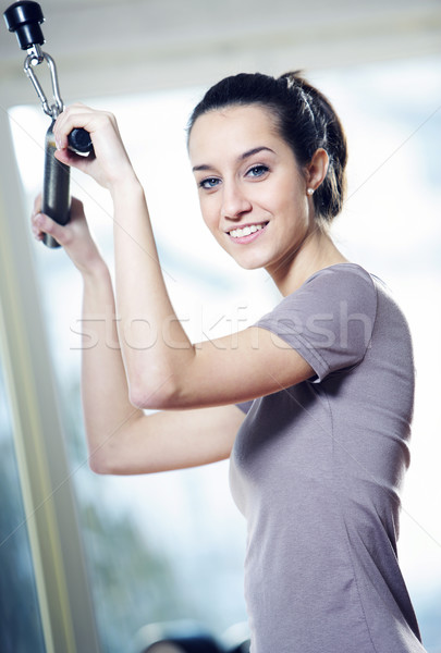 Gülen genç kadın ağırlık makine sağlık kulüp Stok fotoğraf © stokkete