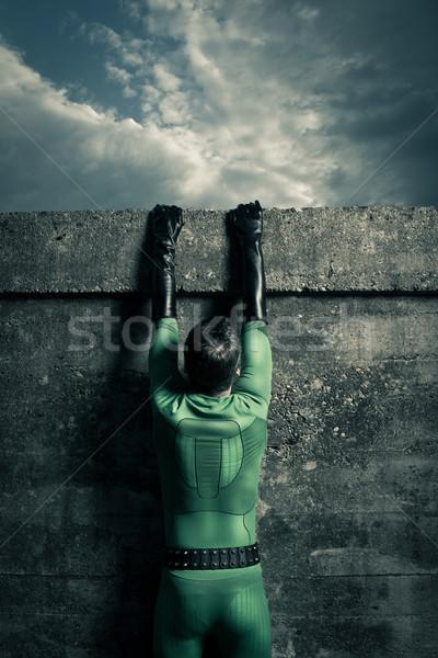 Superhero climbing a wall Stock photo © stokkete