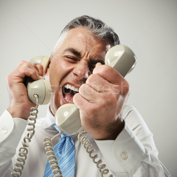 Businessman yelling into phone Stock photo © stokkete