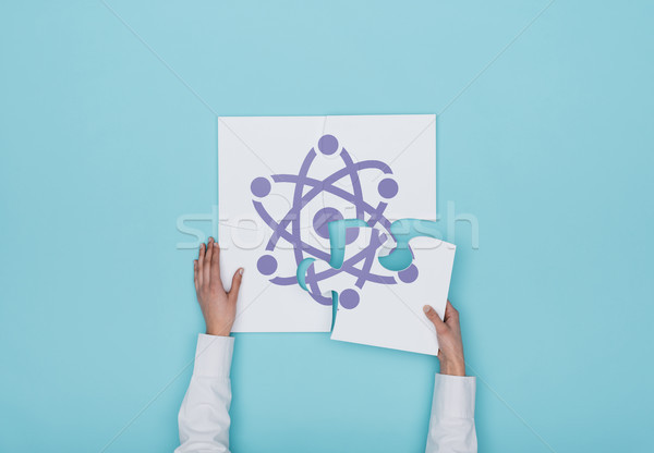 Woman completing a puzzle with atom icon Stock photo © stokkete
