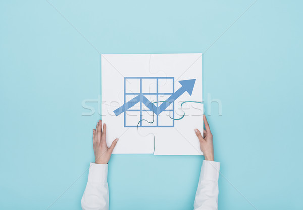 Stock photo: Woman completing a puzzle with a graph icon