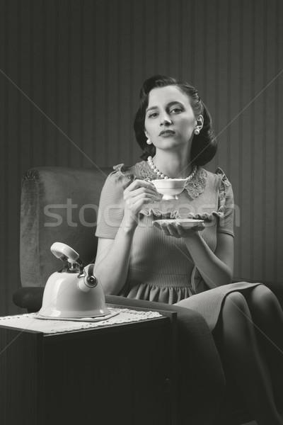 Gyönyörű nő ül fotel iszik tea nő Stock fotó © stokkete