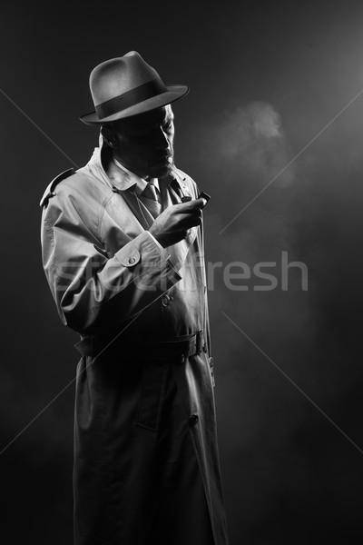 Illuminazione sigaretta bell'uomo trincea cappotto buio Foto d'archivio © stokkete