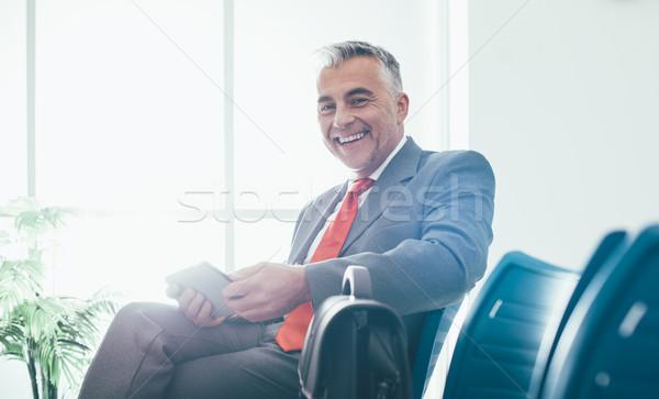 Empresario sala de espera sonriendo sesión digital Foto stock © stokkete