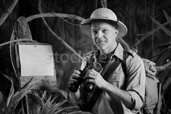 Adventurer in the jungle with binoculars Stock photo © stokkete