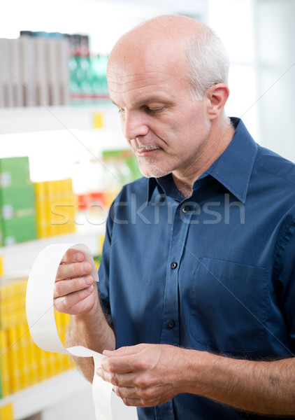 Man checking grocery receipt at store Stock photo © stokkete