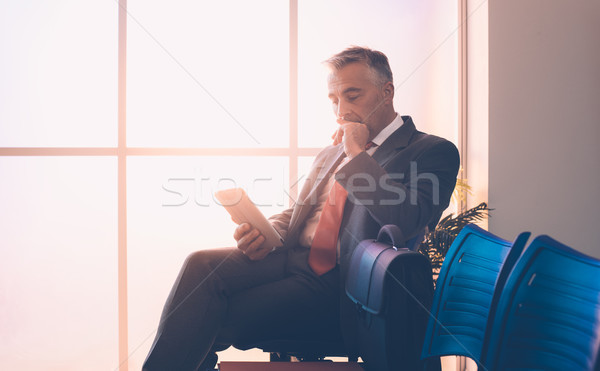 Businessman connecting with his tablet Stock photo © stokkete