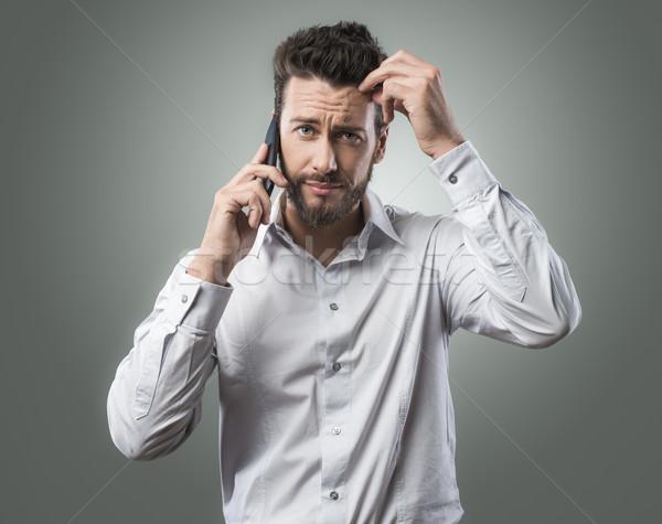 Deluso uomo telefono confusi giovane tecnologia Foto d'archivio © stokkete