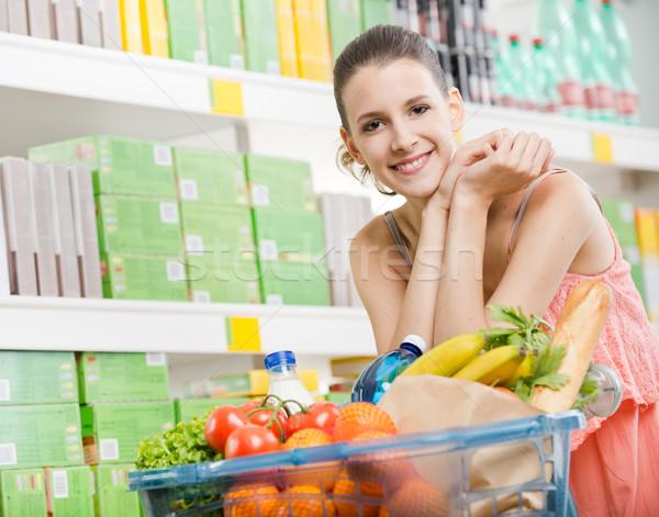 Tele bevásárlókosár mosolyog fiatal nő áruház nő Stock fotó © stokkete
