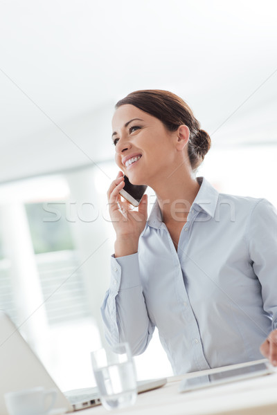 Stock photo: Smiling business woman having a phone call